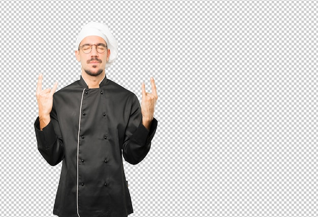 Naughty young chef making a rock gesture