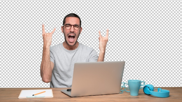 Naughty young man sitting at his desk and doing a rock gesture