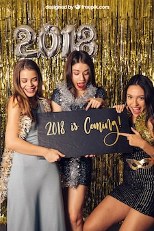 New year mockup with three girls pointing at black board