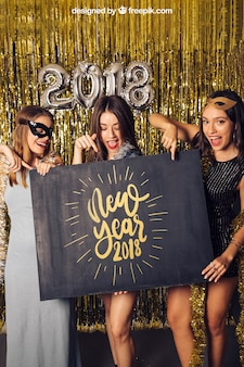 New year mockup with three girls pointing at board