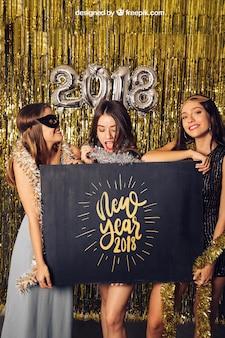 New year mockup with three girls presenting board