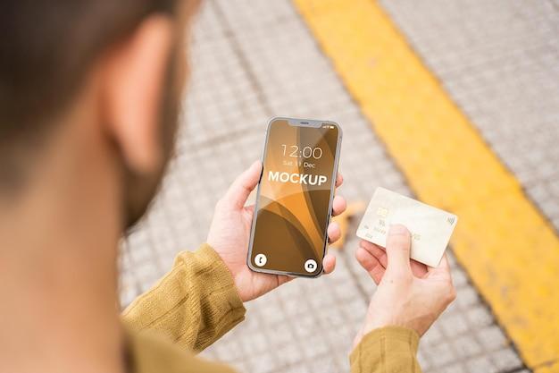신용 카드를 가진 현대인이 들고 있는 멋진 전화 모형