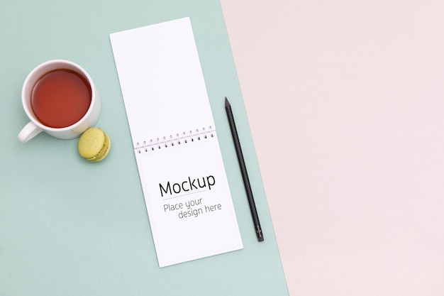 Notebook mockup lay on the office desk with cup of tea and macaron