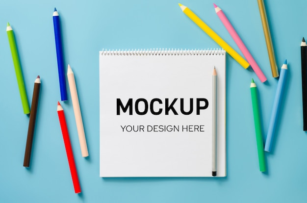 Notebook mockup with set of colorful pencils