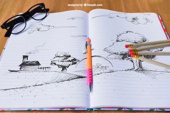 Notebook with drawing of landscape, pencils and glasses