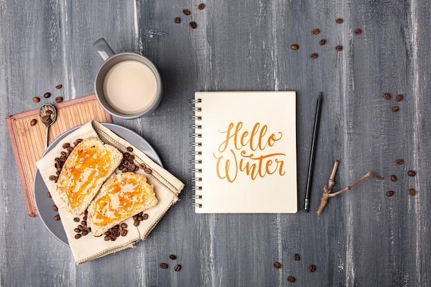 Notebook with hello winter message beside breakfast