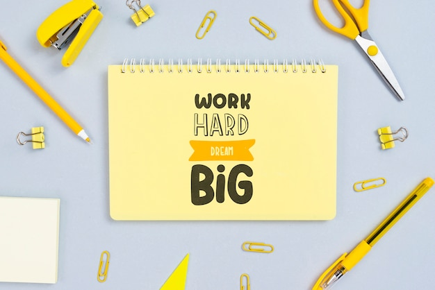 Notebook with positive message and office tools beside