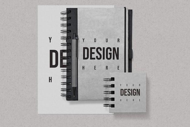 Блокноты и бумажный макет на сером фоне