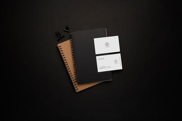ノートブックと黒の背景に黒の要素を持つ名刺のモックアップ
