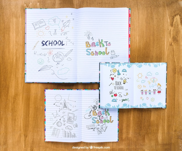 Notebooks with drawings on wooden table