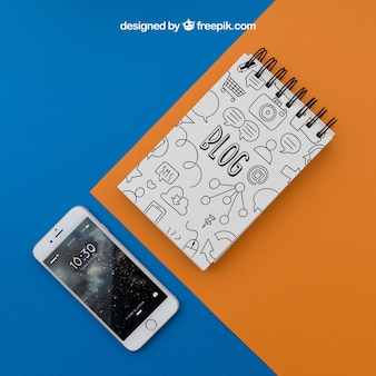 Notepad and smartphone on orange and blue background