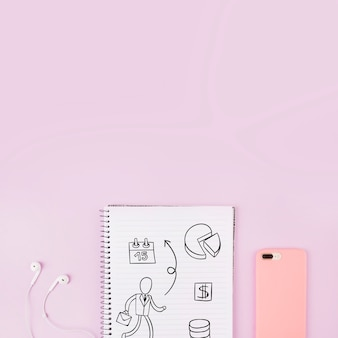 Notepad mockup next to smartphone and earphones
