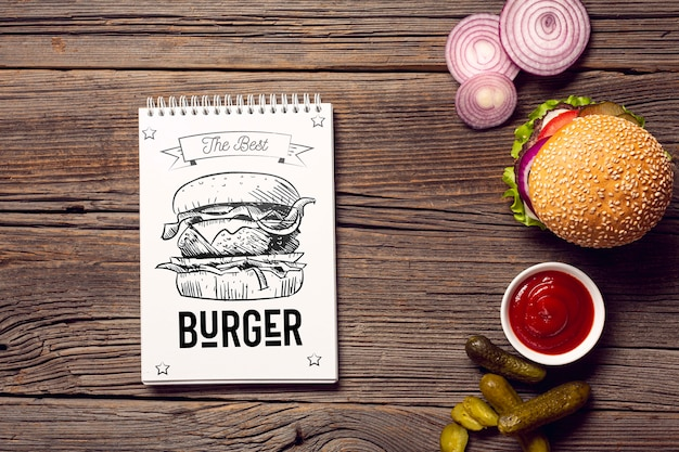 Notepad with burger sketch on wooden background