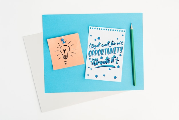 Notepad with motivational quote flat lay
