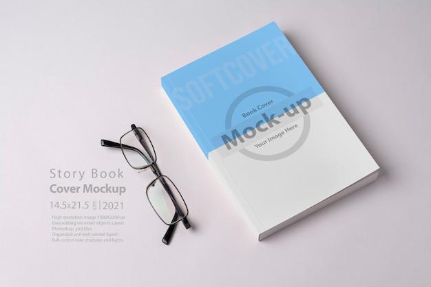빈 표지 모형이있는 소설 책과 안경