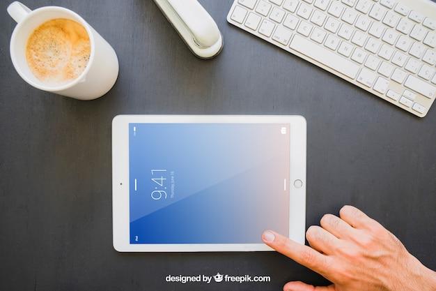 사무실 책상과 손가락 가로 태블릿을 만지고