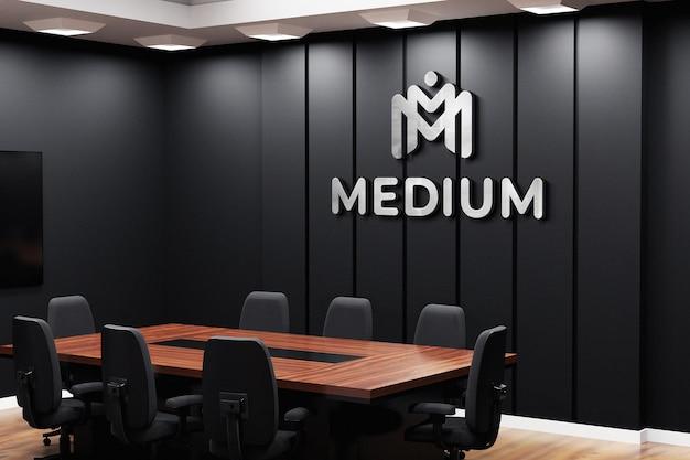 Макет логотипа офиса на черной стене в конференц-зале