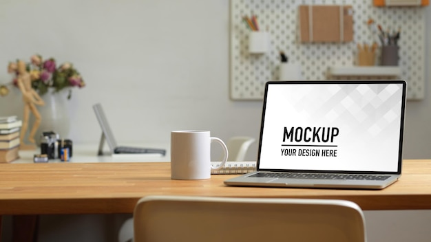 Office room with laptop mockup on the table with office supplies Premium Psd