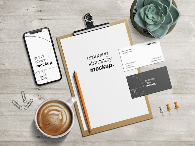 クリップボードのレターヘッド、名刺、スマートフォンのモックアップテンプレートが設定されたオフィス文具デスク