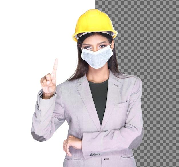 사무실 여성 회색 정장은 산업용 먼지 마스크를 쓴 노란색 안전 모자를 쓰고 터치 스크린 손가락 기호를 보여주고 클라이언트 건축가 여성은 covid-19, 격리된 스튜디오에서 보호용 얼굴 마스크를 착용합니다.