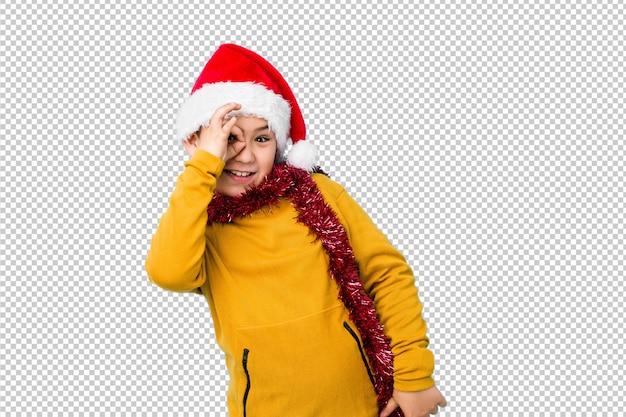 孤立したサンタの帽子をかぶってクリスマスの日を祝う少年は、目で[ok]ジェスチャーを維持する興奮していた。