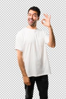 目をウインクしながら指でokの標識を示す白いシャツを持つ若者