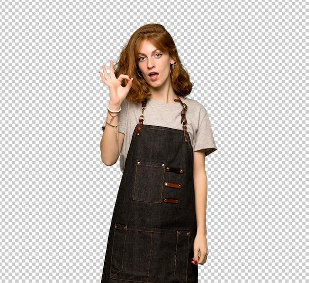 指でokの標識を示すエプロンを持つ若い赤毛の女性