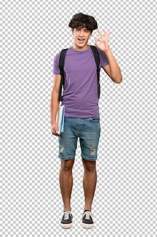 Okサインと親指ジェスチャーを示す若い学生男