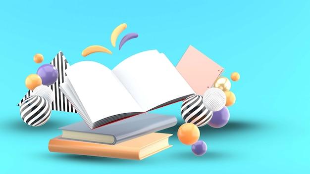 Открытая книга и тетрадь в окружении разноцветных шариков на синем