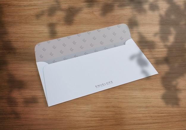 Открытый конверт на деревянном столе с тенями