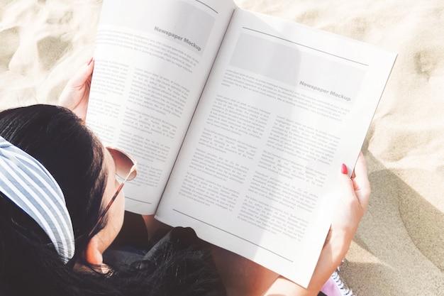 Открытая газета в руках девушки, макет пляжной сцены
