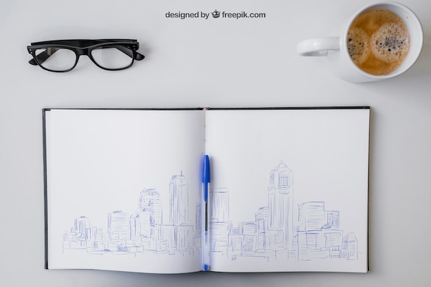 Open notebook with pen drawing, glasses and coffee