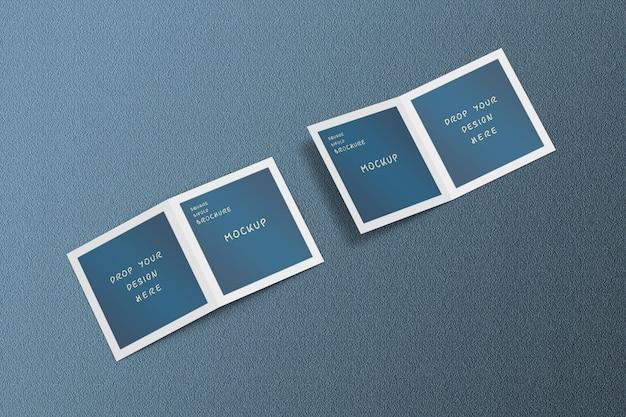 開いて、高角度で正方形のパンフレットのモックアップをカバー