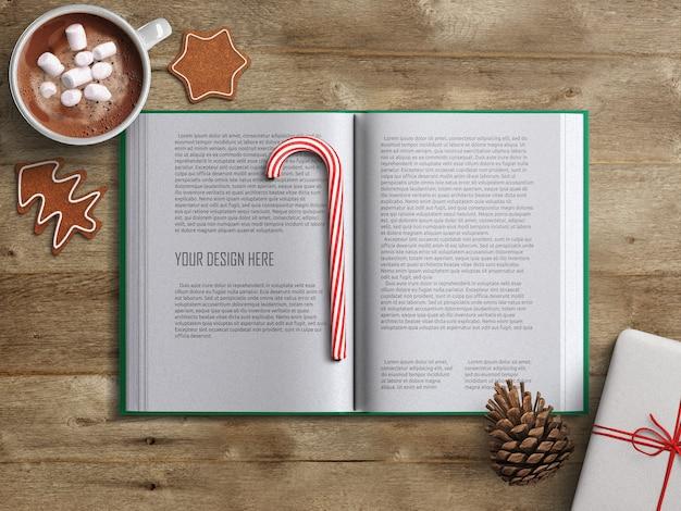 木製のテーブルにクリスマスの装飾が施された開いた本のページのモックアップ
