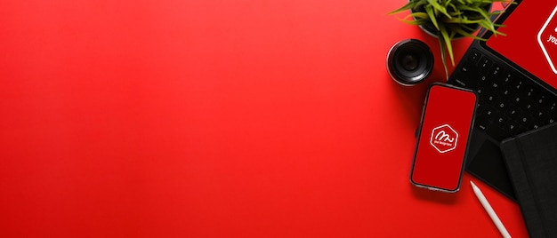 Overhead shot of bright red desk with office supplies and mockup
