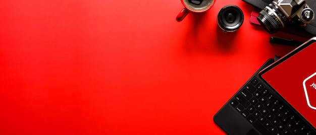 Overhead shot of bright red photographer desk with office supplies