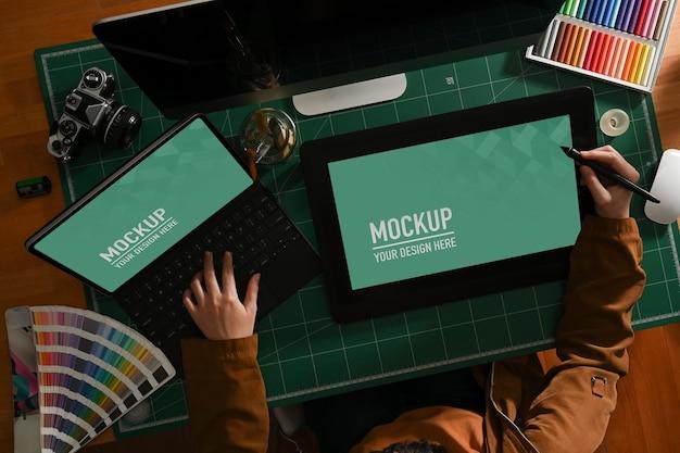 Верхний снимок девушки-графического дизайнера, работающей с макетом планшета и ноутбука на компьютерном столе