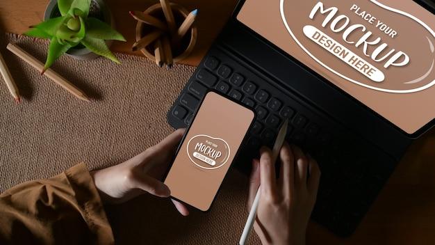 Верхний снимок женской руки, держащей макет смартфона во время работы с макетом планшета