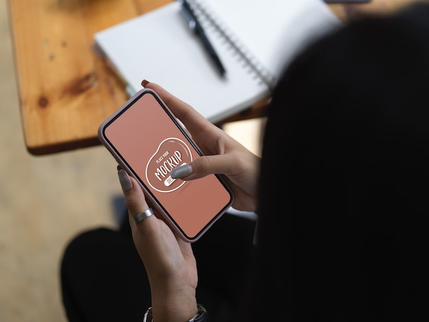 작업 테이블에 앉아있는 동안 스마트 폰을 모의에 여성 문자 메시지의 오버 헤드 샷