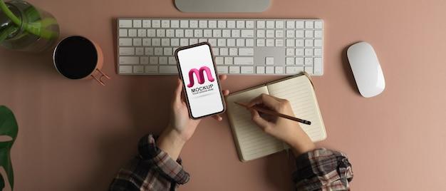 Снимок сверху: фрилансер использует макет смартфона и делает заметку во время работы за компьютерным столом