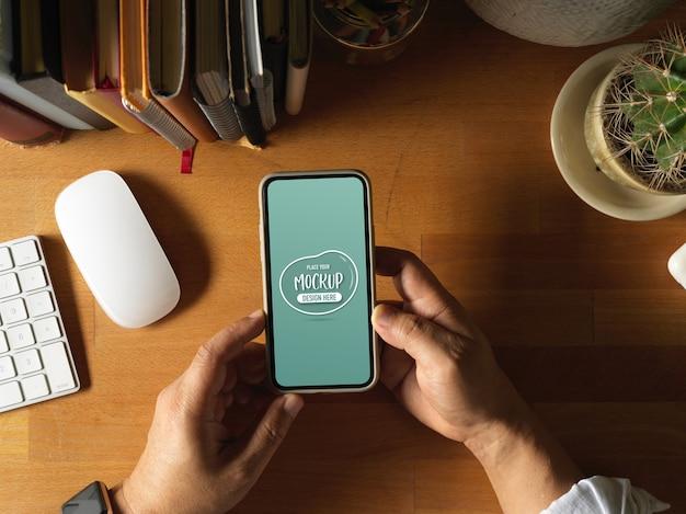 Верхний снимок мужских рук, держащих макет смартфона на деревянном рабочем столе