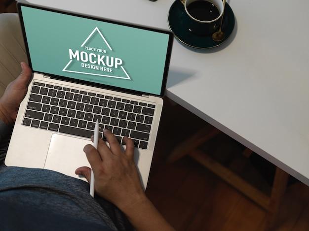 ノートパソコンのモックアップを扱う男性会社員のオーバーヘッドショット