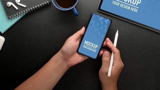 黒いテーブルにスタイラスペンを保持しながらモックアップスマートフォンを使用して男性のオーバーヘッドショット