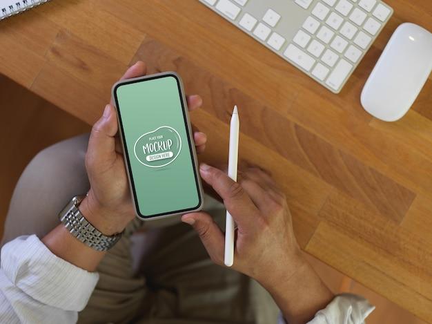 Верхний снимок рук мужского работника, держащего макет смартфона во время работы за офисным столом