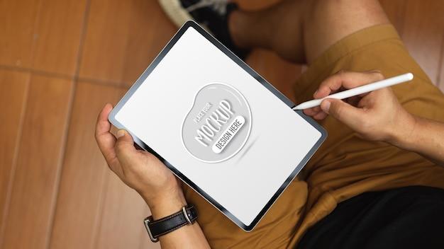 그의 사무실 방에 앉아있는 동안 태블릿을 모의로 작업하는 젊은 남자의 오버 헤드 샷