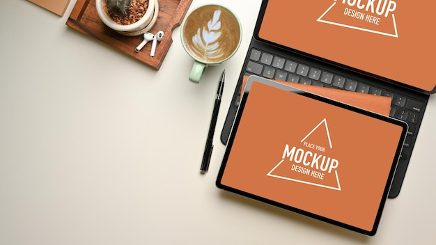 Overhead shot of workspace with two digital tablet mockup, coffee cup and stationery, top view
