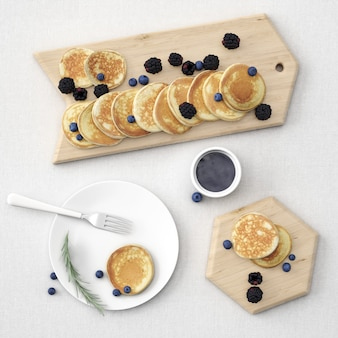 Pancakes on board and plate with berries