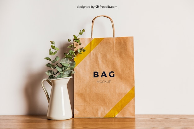 Paper bag mockup next to flower pot