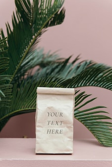 Paper bag mockup in a pastel pink room by a palm tree