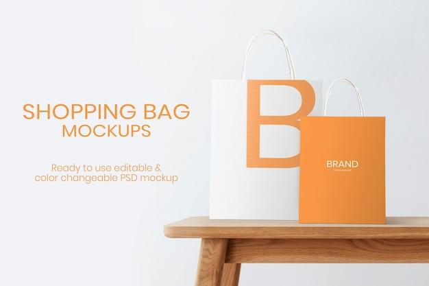 Sacchetti di carta mockup psd per lo shopping e il marchio su un tavolo di legno